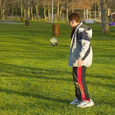 Boy Juggling or Football in The Background?