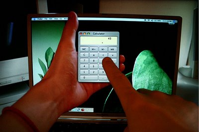 Hand Holding a Calculator Inside The Monitor